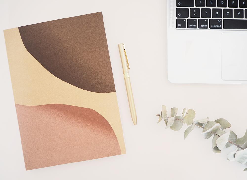 Arbeitsplatz Texterin und Content Creator mit Notizbuch, Stift und Laptop